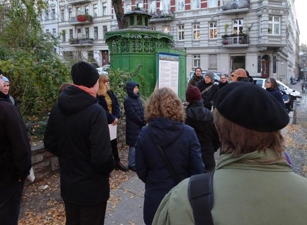 Eine Gruppe Menschen steht auf dem Bürgersteig und hört einem Mann zu.