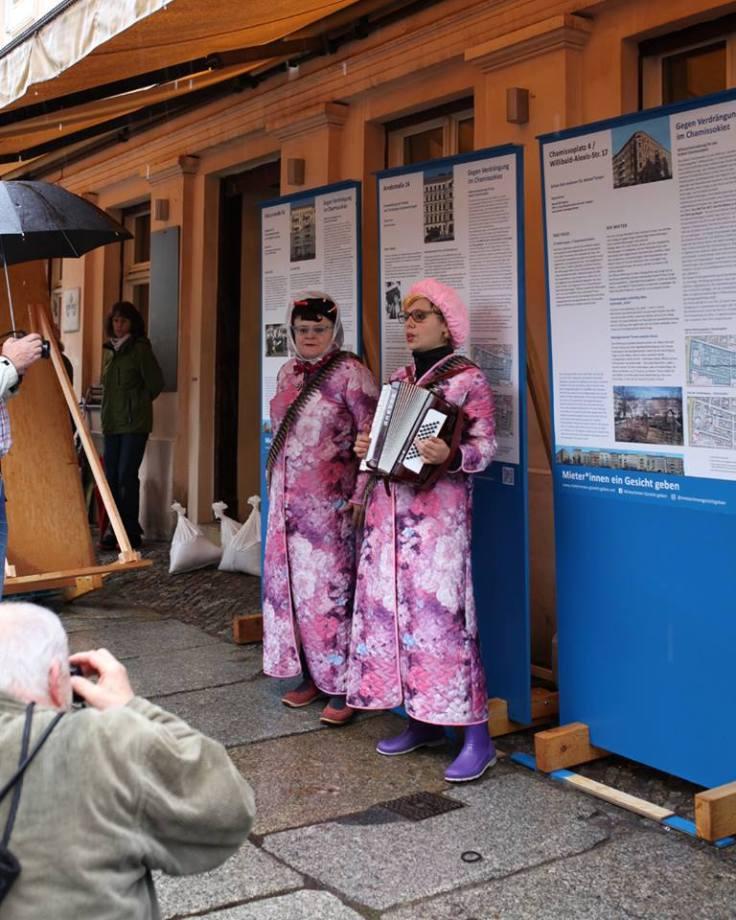 Zwei Frauen in pinken Bademänteln stehen vor Stellwänden und musizieren